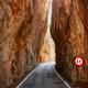 Narrow road cut through a mountain. - PhotoDune Item for Sale