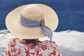 Summer time. Woman with hat and blue water background. Relaxing - PhotoDune Item for Sale
