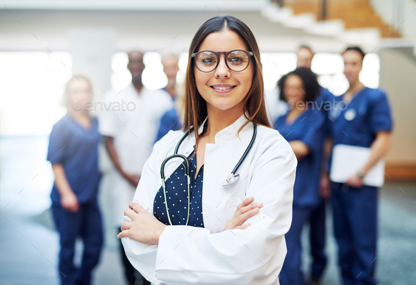 Young pretty female doctor standing in clinic - Stock Photo - Images