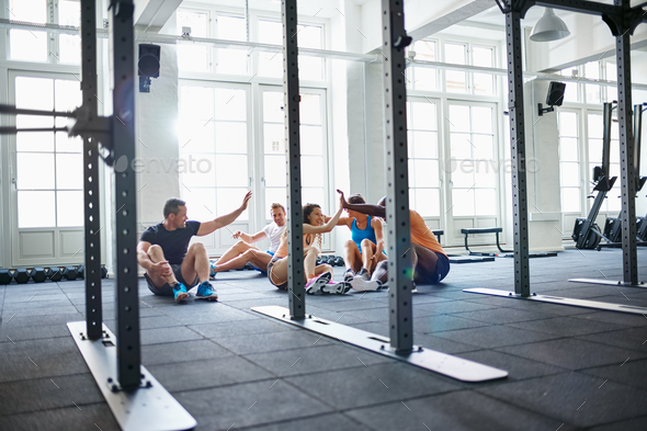 Smiling friends sitting on a gym floor high fiving together - Stock Photo - Images