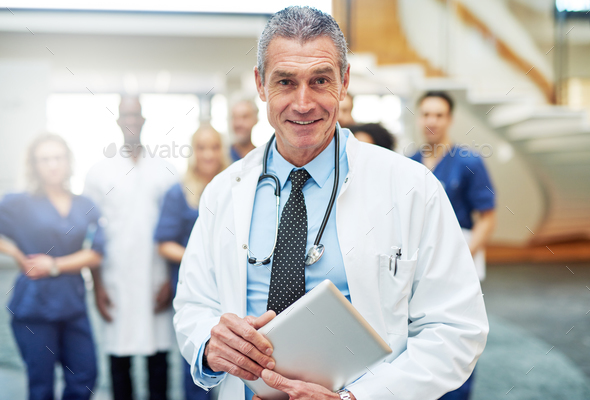 Cheerful mature doctor with tablet in hospital - Stock Photo - Images