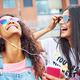 Young girlfriends sitting outside together listening to music on earphones - PhotoDune Item for Sale