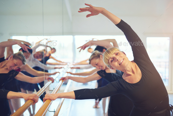 Smiling mature woman stretching in ballet class - Stock Photo - Images