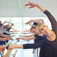 Smiling mature woman stretching in ballet class - PhotoDune Item for Sale