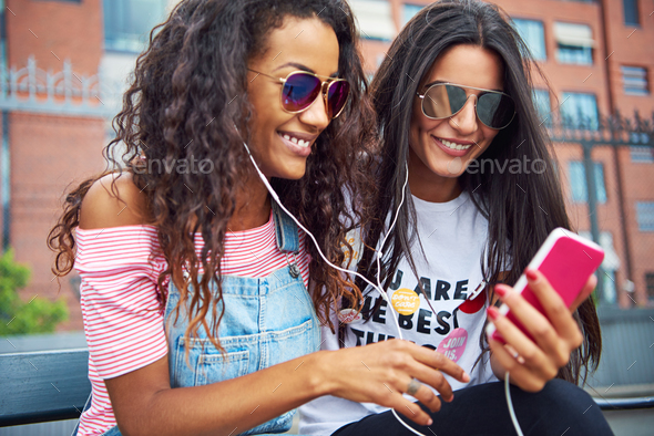 Young girlfriends sitting together outside streaming video on a smartphone - Stock Photo - Images