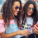Young girlfriends sitting together outside streaming video on a smartphone - PhotoDune Item for Sale