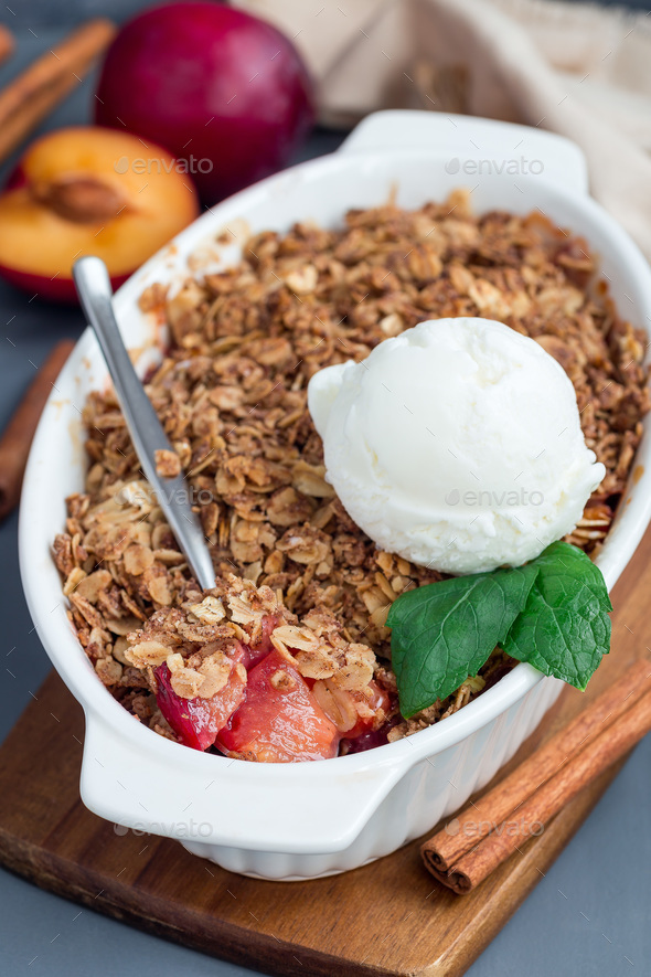 Plum crumble pie or plum crisp with oats and spices, served with - Stock Photo - Images