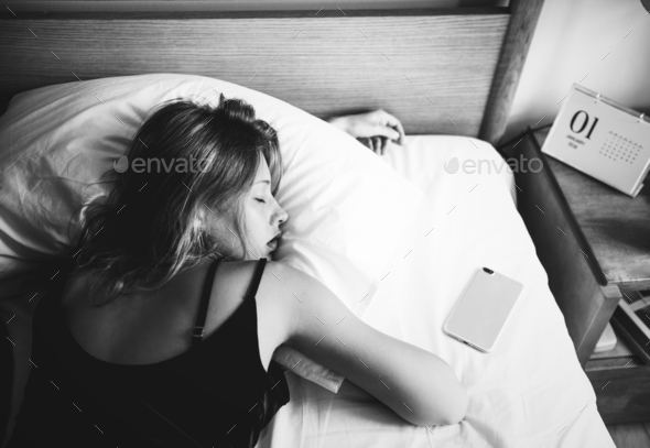 A Caucasian woman sleeping on her bed - Stock Photo - Images