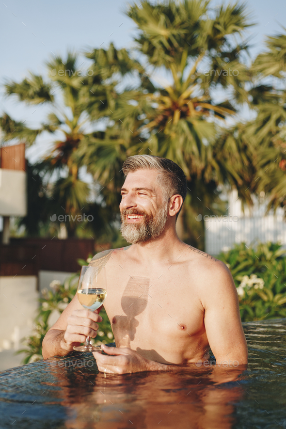 Handsome man having a glass of wine in the pool - Stock Photo - Images