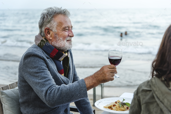 Seniors toasting with red wine at the beach - Stock Photo - Images