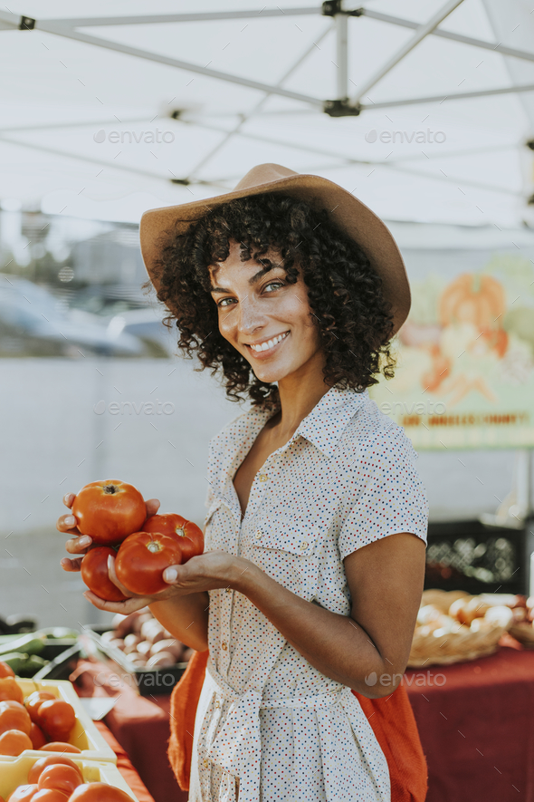 Woman buying tomatoes at a farmers market - Stock Photo - Images