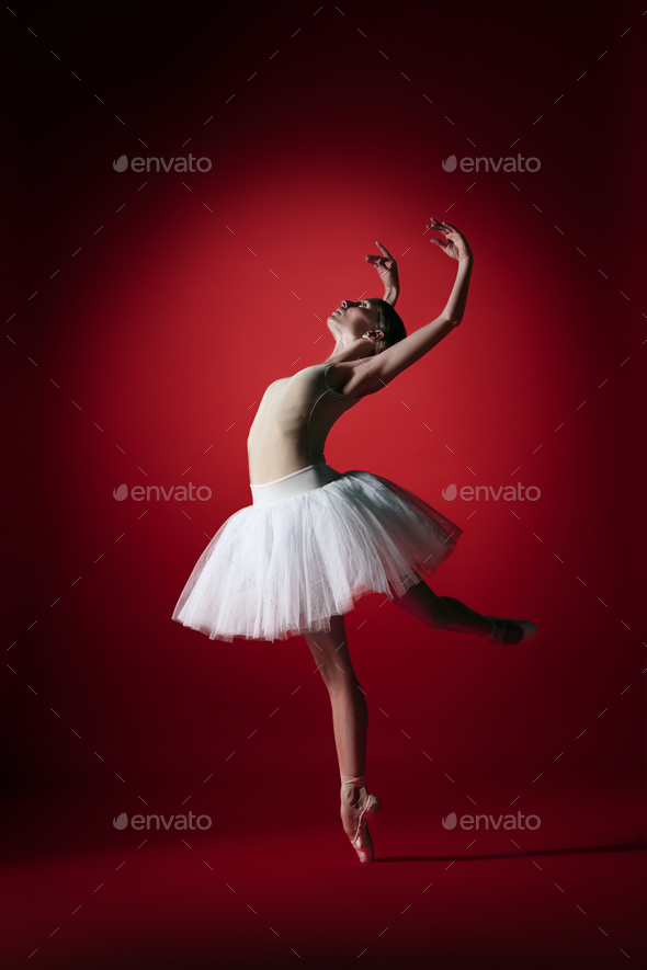 Ballerina. Young graceful female ballet dancer dancing at red studioskill. Beauty of classic ballet. - Stock Photo - Images