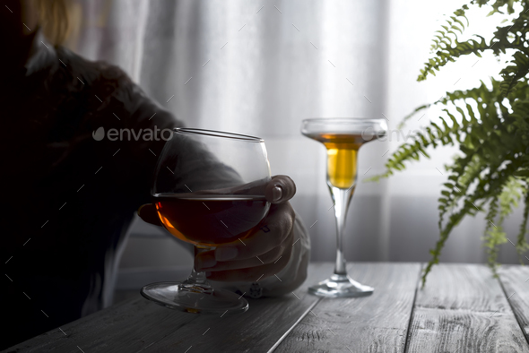 silhouette of anonymous alcoholic woman person drinking behind glass of alcohol. - Stock Photo - Images