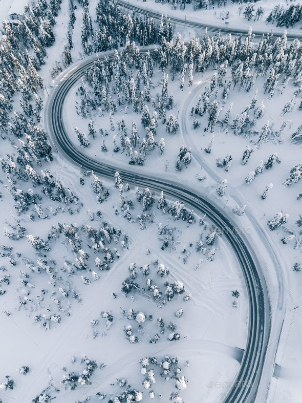Aerial view of winter road in the forest covered with snow, Finland Lapland - Stock Photo - Images
