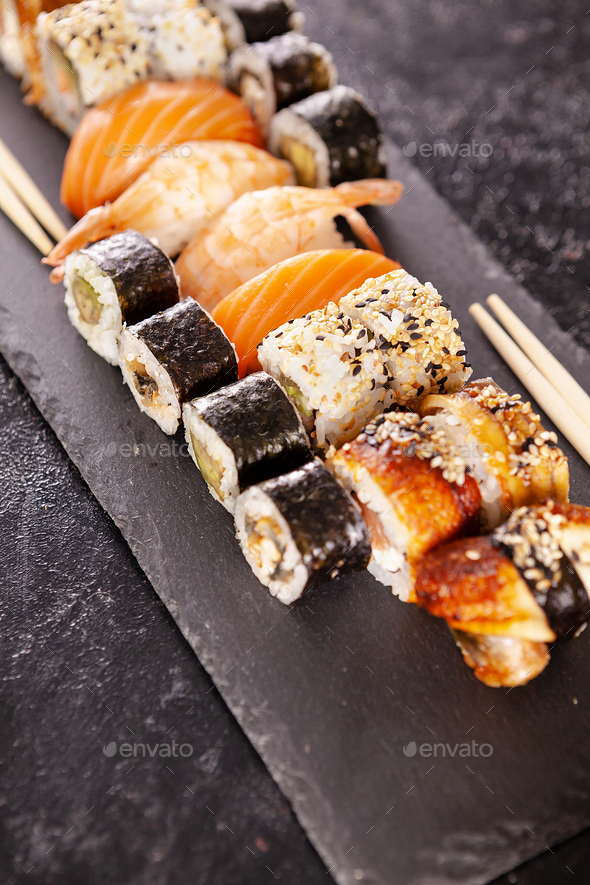 Plate with variety of sushi on a dark stone - Stock Photo - Images