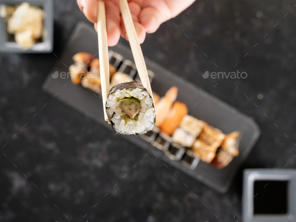 Chopstick with a sushi in focus and a mix of sushi on dark stone - Stock Photo - Images