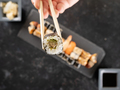 Chopstick with a sushi in focus and a mix of sushi on dark stone - PhotoDune Item for Sale