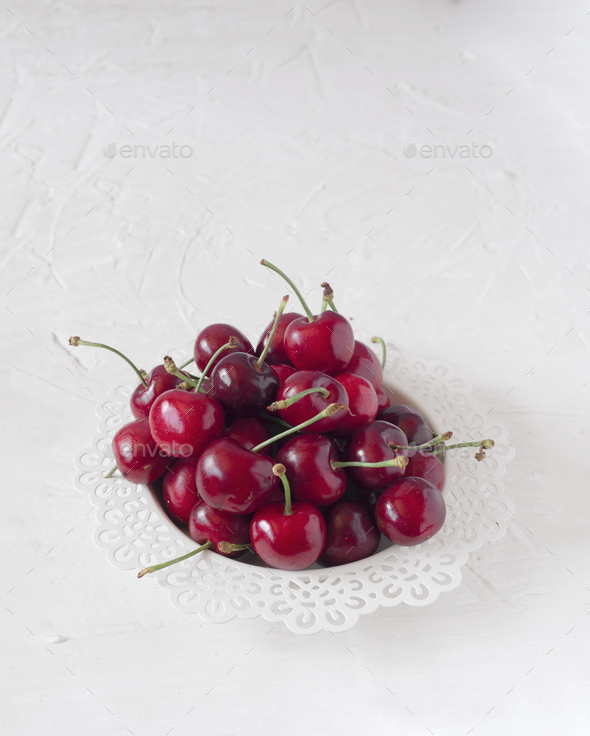 ripe cherries on white board painted with chalk Stock Photo by Jultud