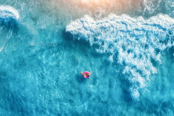 Aerial view of slim young woman swimming on the donut swim ring - Stock Photo - Images