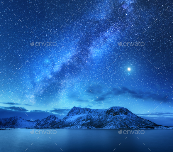Milky Way over snow covered mountains and sea at night in winter Stock Photo by den-belitsky