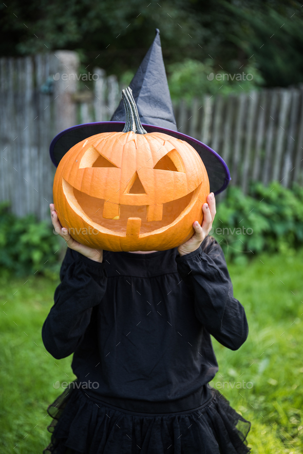 Funny girl with halloween pumpki in garden - Stock Photo - Images