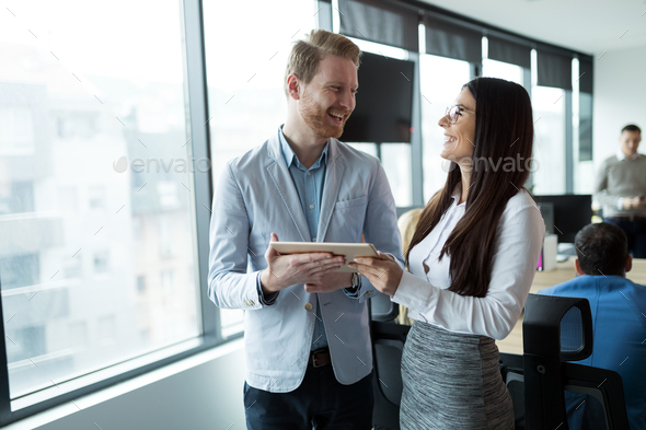Businesspeople discussing while using digital tablet in office - Stock Photo - Images