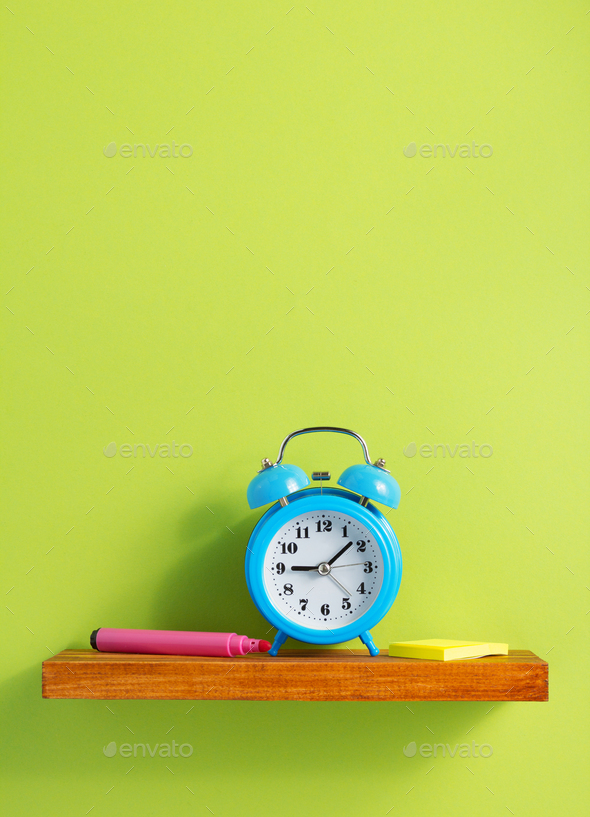 alarm clock on shelf at wall background - Stock Photo - Images