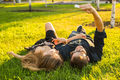 Teenage couple lying on grass and taking selfie on smartphone - PhotoDune Item for Sale