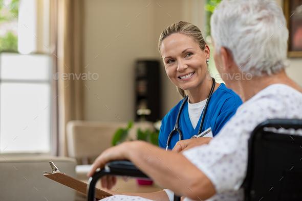 Friendly nurse talking to senior patient - Stock Photo - Images
