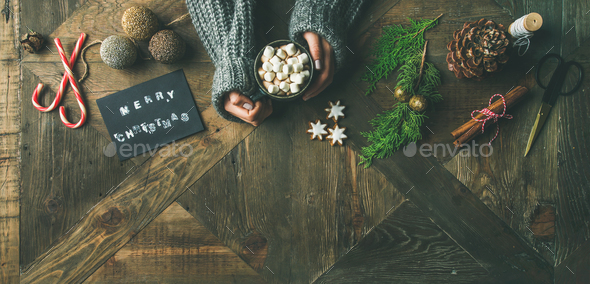 Flat-lay of greeting card, glittering toy, woman's hands holding mug - Stock Photo - Images