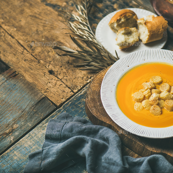 Fall pumpkin cream soup with croutons and seeds, square crop - Stock Photo - Images