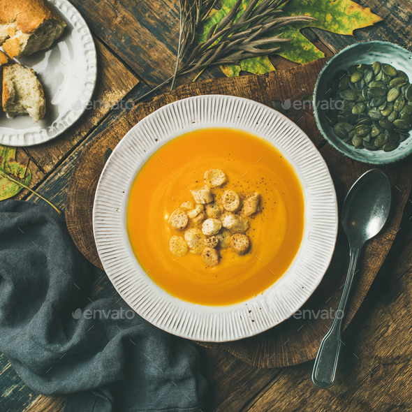 Warming pumpkin cream soup with croutons and seeds, square crop - Stock Photo - Images
