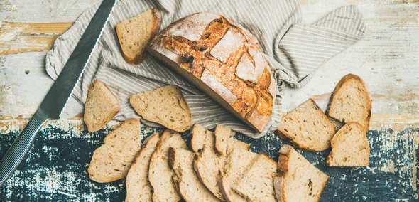 Sourdough wheat bread cut in slices on table, wide composition - Stock Photo - Images