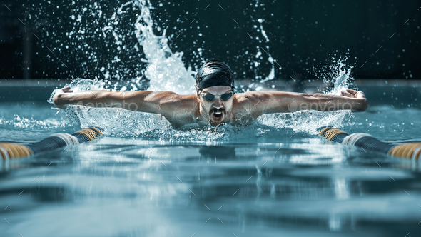 dynamic and fit swimmer in cap breathing performing the butterfly stroke - Stock Photo - Images