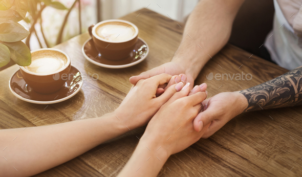Young couple in love holding hands in cafe - Stock Photo - Images