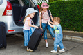 two little girls  and boy standing near the car with backpacks - PhotoDune Item for Sale