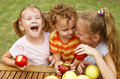 three happy children sitting at the table and eat apples - PhotoDune Item for Sale