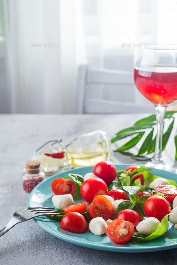 Caprese salad. Healthy meal with cherry tomatoes, mozzarella balls, spices, fresh rocket - Stock Photo - Images