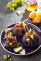 Gourmet appetizer of baked figs with goat cheese,walnuts and honey on ceramic plate - PhotoDune Item for Sale
