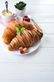 breakfast freshly baked croissant decorated with jam and chocolate, flowers on wooden table - PhotoDune Item for Sale