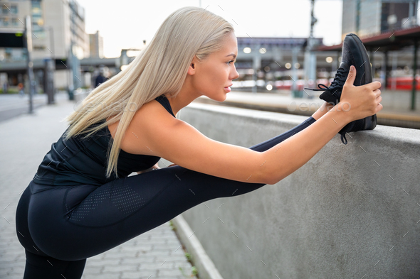 Determined Young Woman Stretching Leg On Railing In City - Stock Photo - Images