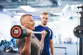 Older man lifting weights, supervised by gym assistant. - PhotoDune Item for Sale