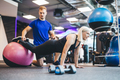 Woman working out on a ball with personal trainer. - PhotoDune Item for Sale