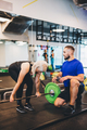 Personal trainer assisting woman lifting weights. - PhotoDune Item for Sale