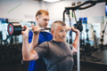 Senior man lifting weights with help of gym assistant. - PhotoDune Item for Sale