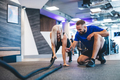 Gym instructor and a woman exercising at the gym. - PhotoDune Item for Sale