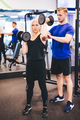 Exercising woman assisted by personal trainer. - PhotoDune Item for Sale