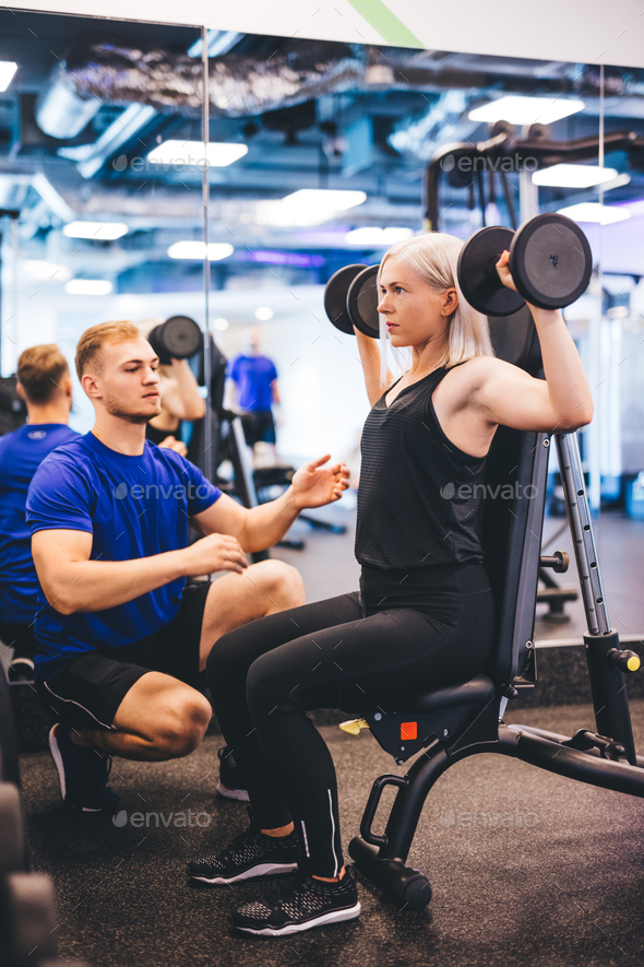 Woman lifting weights, exercising with personal trainer. - Stock Photo - Images