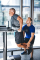 Man helping senior man with his workout at a gym. - PhotoDune Item for Sale