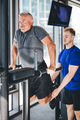 Gym instructor helping senior man at the gym. - PhotoDune Item for Sale